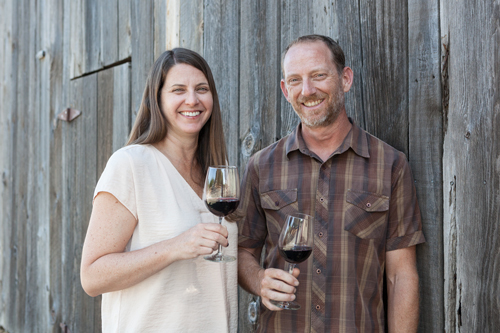 shadow ranch winery owners smiling at the camera with a glass of red wine